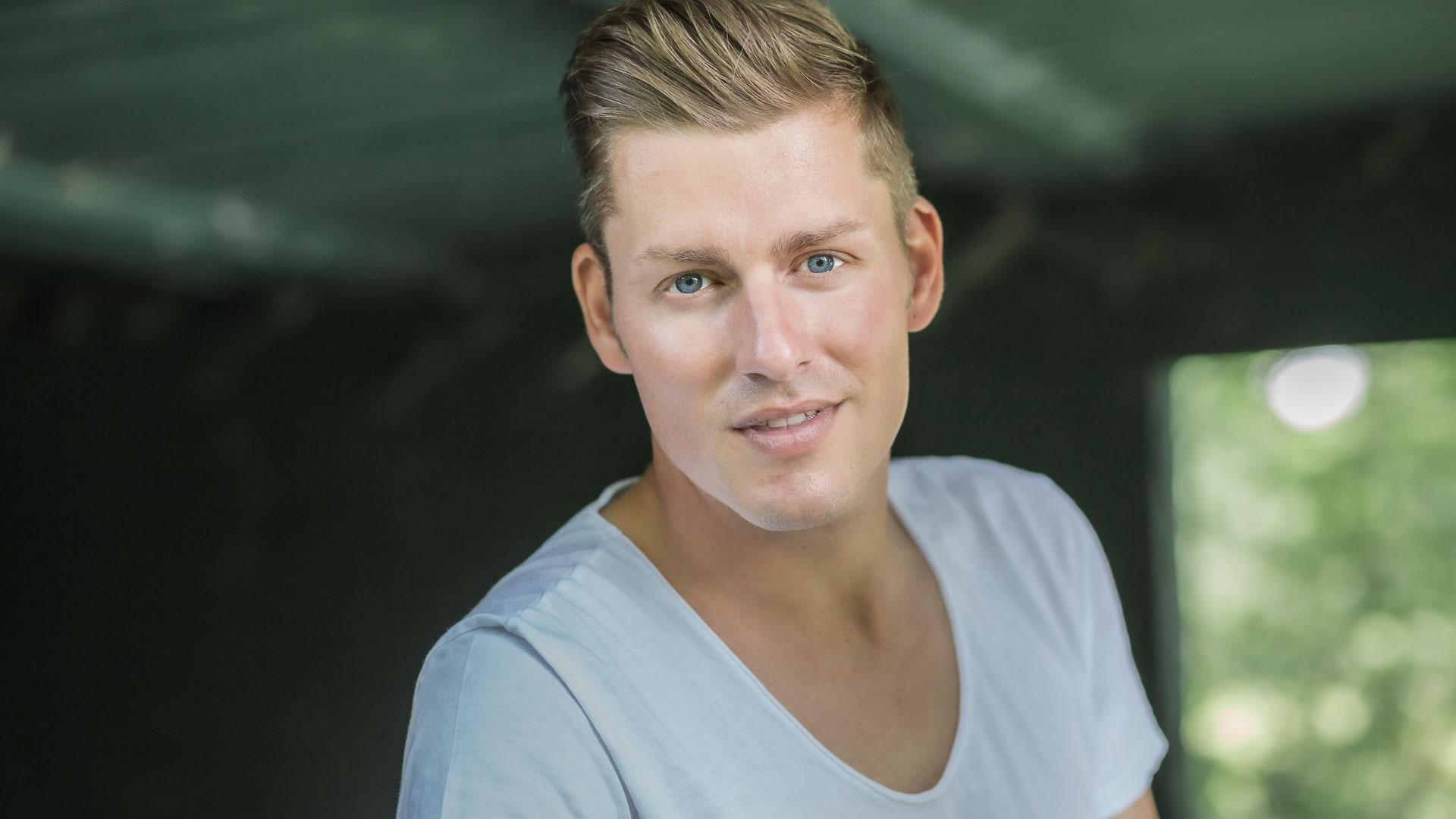 Online-Dating-Fotos: Profilfoto eines jungen, blonden Mannes mit blauen Augen, der sypathisch in die Kamera lächelt.