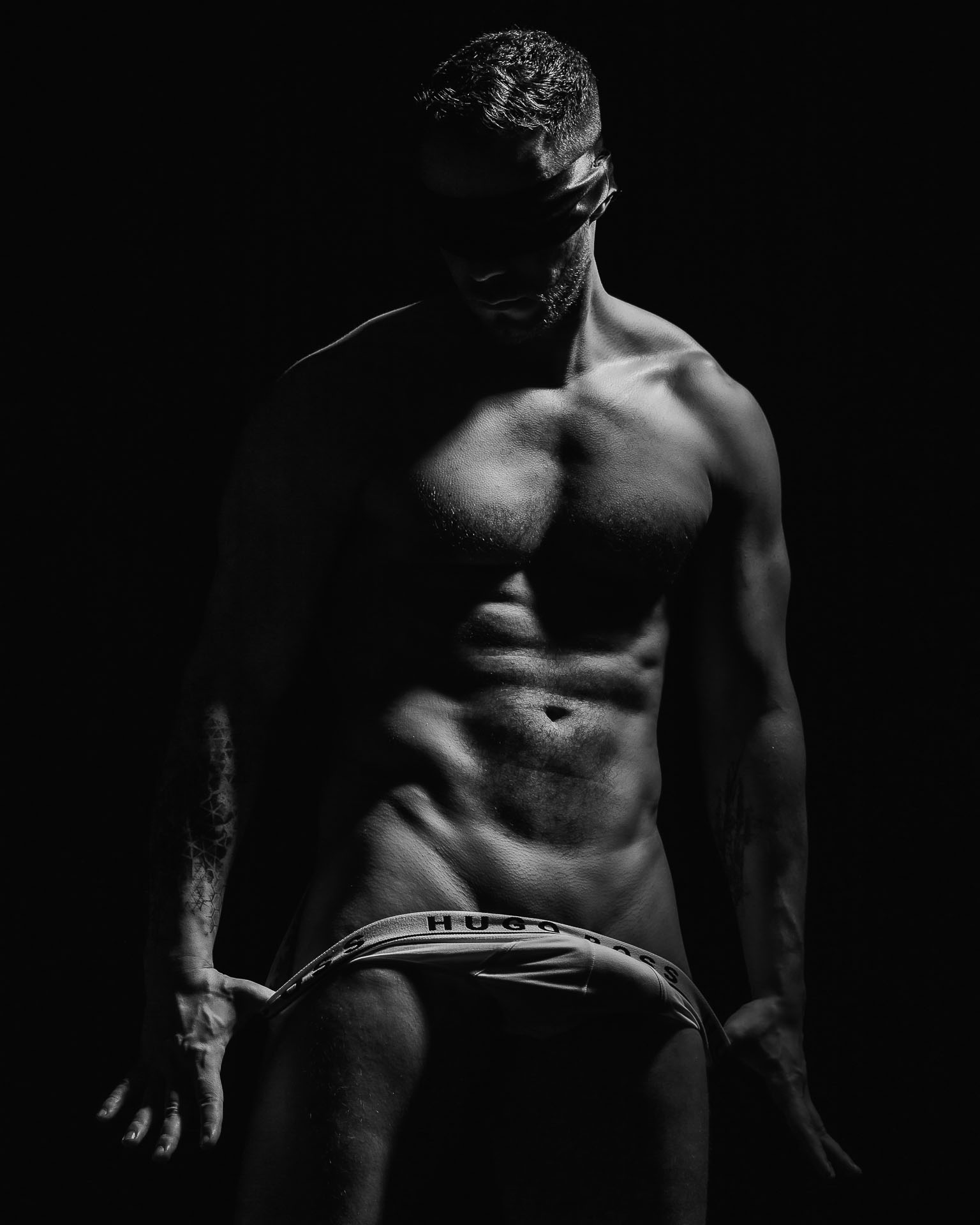 erotisches Männershooting, Mann mit einem Sixpack und Unterhose und in einer erotischen Pose