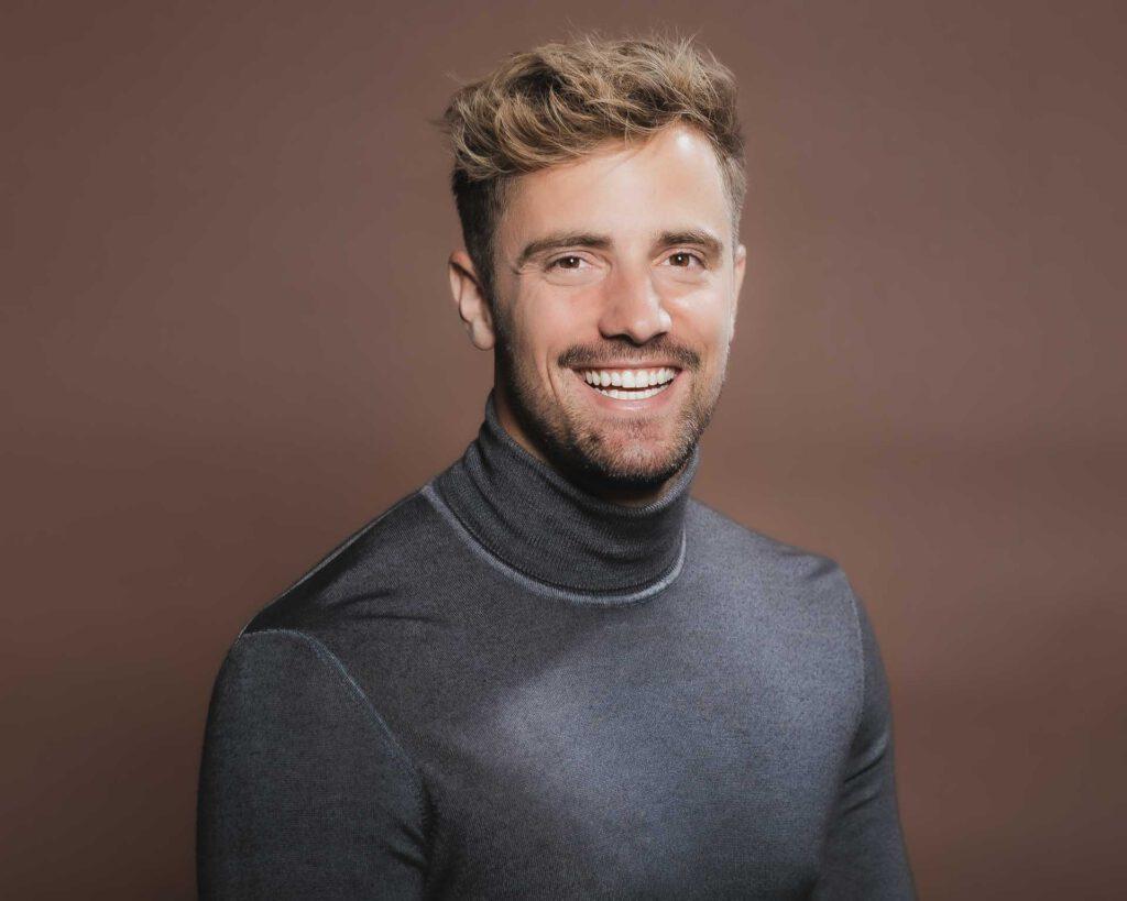 Professionelles Online Dating Foto mit einem sehr gut aussehenden, jungen Mann in einem grauen Pullover, der lächelt.