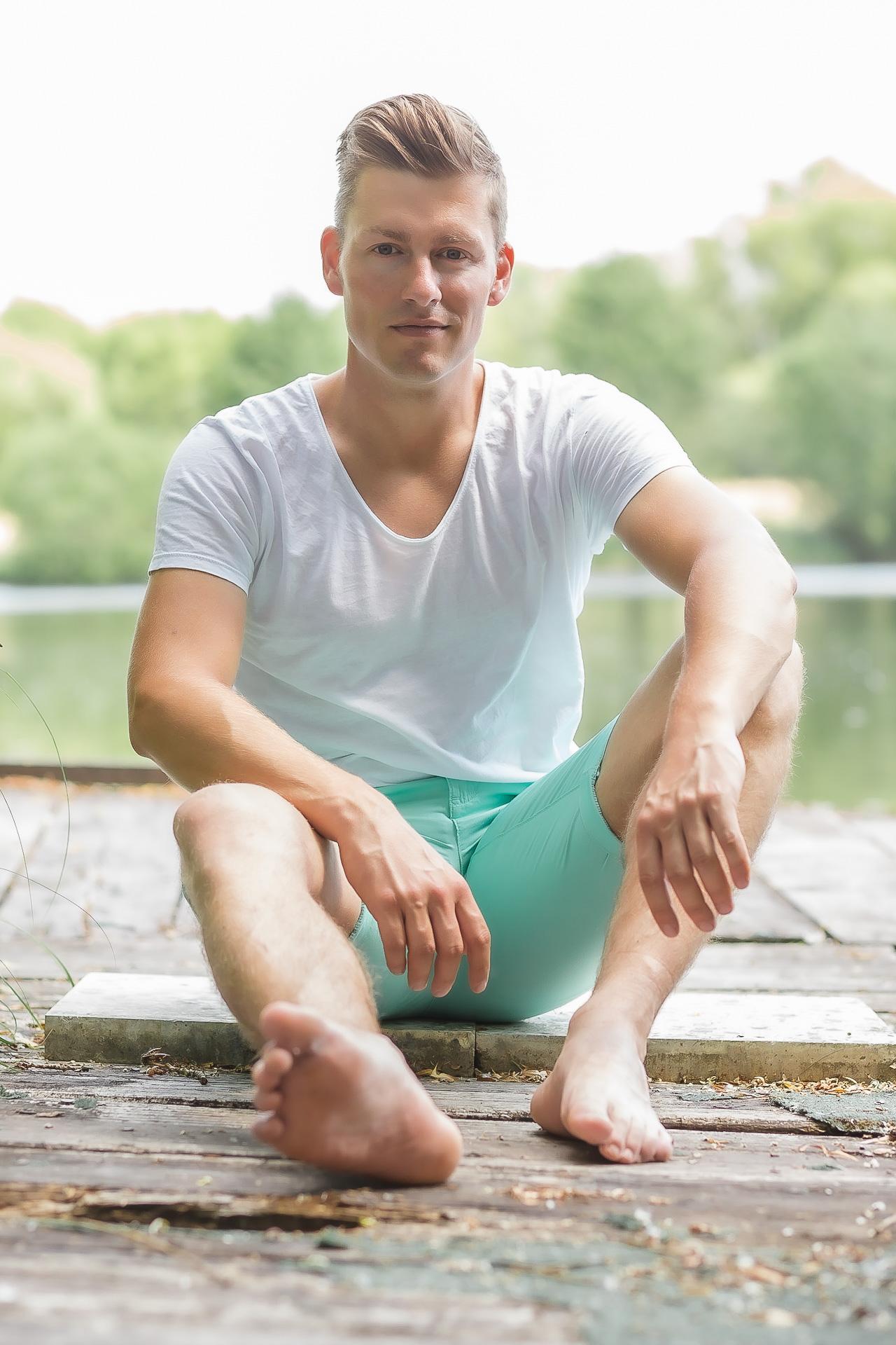 Online-Dating-Fotos mit einem blonden, gutaussehenden, jungen Mann, der mit einer kurzen grünen Hose aus einem Steg am See sitzt.r-schneller-Sex