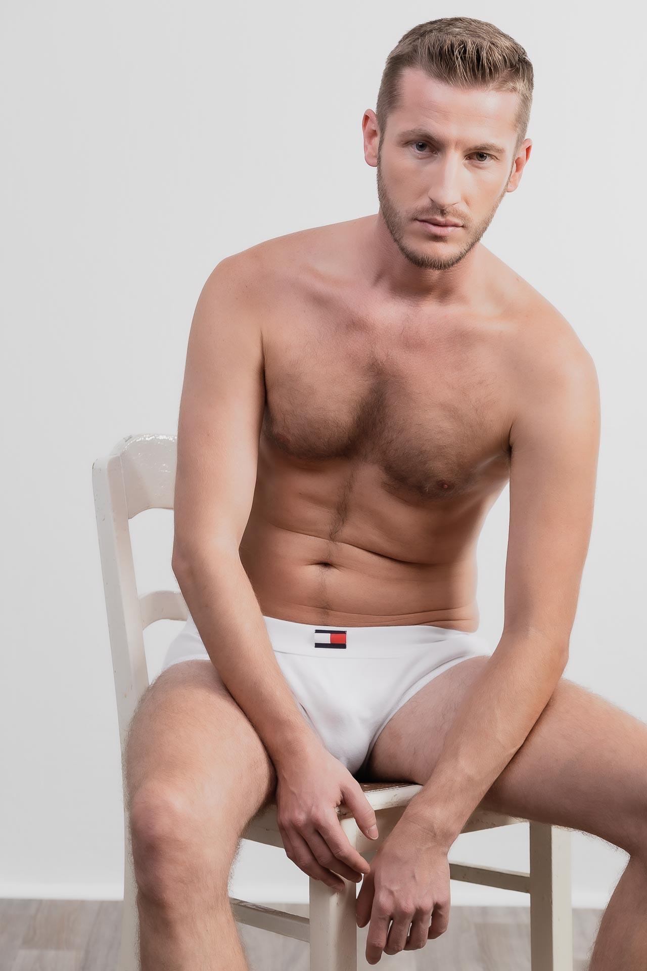 Erotisches Männershooting, Mann sitzt mit einer weißen Unterhose auf einem Stuhl